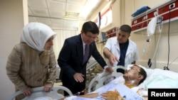 Премьер-министр Турции Ахмет Давутоглу (второй слева) в сопровождении своей супруги посещает раненых после теракта в городе Суруч, 21 июля 2015 года.