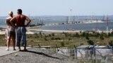 Люди рядом с российским городом Тамань смотрят на строительство Керченского моста. Протяженность перехода – 19 километров. На круглосуточном строительстве занято около пяти тысяч человек. К реализации проекта приступили в мае 2015 года.