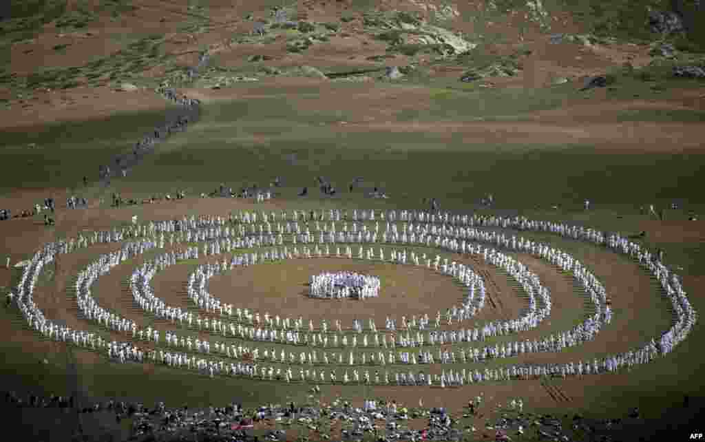"Members of an international religious movement called the White Brotherhood perform a ritual dance on the top of Rila Mountain, near Babreka Lake, Bulgaria. More than 1,500 pilgrims gathered to mark their ""spiritual"" new year with a collective meditative dance they believe connects them to cosmic rhythms and beats the blues. (AFP/Nikolay Doychinov)"