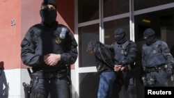 Испания полициясы терроризмге күдіктіні ұстап әкетіп барады. Каталония, сәуір 2015 жыл. (Көрнекі сурет)