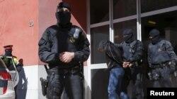 """Каталония полициясы күдікті """"содырларды"""" тұтқындап әкетіп барады. Испания, 8 сәуір 2015 жыл."""