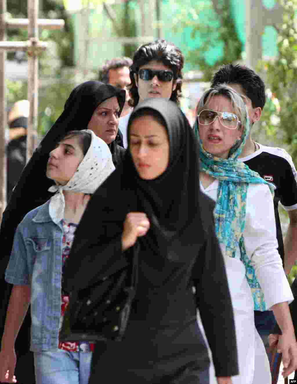 Iranian women in traditional and modern dress walk in Tehran. Some women say they dress conservatively in public but more daringly in their private lives.