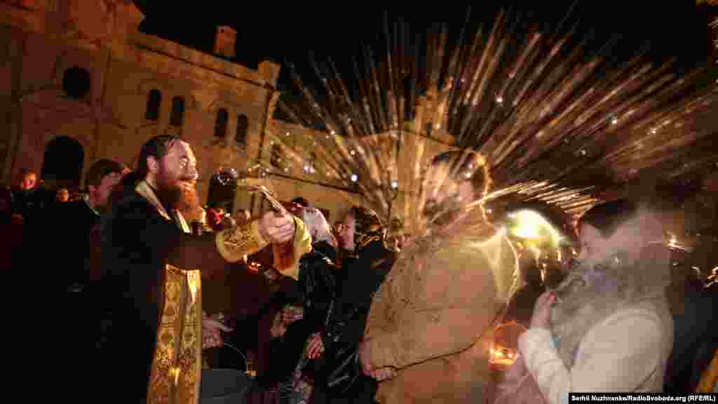 Священники окроплюють святою водою вірян та пасхальні кошики