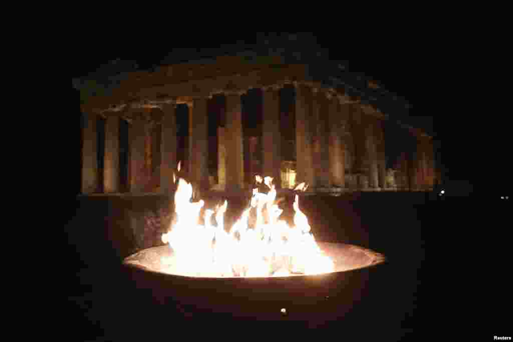 An Olympic flame is lit at an altar during the torch relay of the Sochi 2014 Winter Olympics in front of the Parthenon at the Acropolis hill in Athens. (Reuters/Yorgos Karahalis)