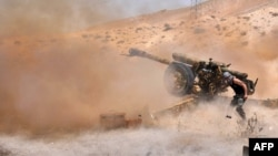 Një ushtar sirian duke hapur zjarr artilerik kundër IS-it në Palmira