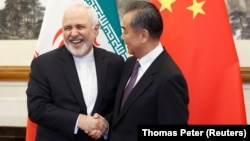 Chinese Foreign Minister Wang Yi (right) greets Iranian counterpart Mohammad Javad Zarif in Beijing on May 17.