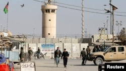 Afghan National Army soldiers and police keep watch outside the Bagram airfield entrance gate, after an explosion at the NATO air base, north of Kabul, on November 12.