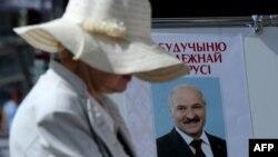 Женщина рядом с предвыборным плакатом, на котором изображен действующий президент и кандидат в президенты Беларуси Александр Лукашенко. Минск, 23 июля 2015 года.