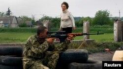 Žena prelazi most pored ruskog militanta, Slavjansk, 15. maj 2014.