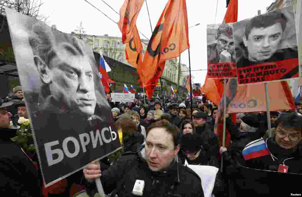 Petr Tsarkov, co-chairman of the Solidarity opposition movement, holds a poster of Nemtsov during the memorial march.