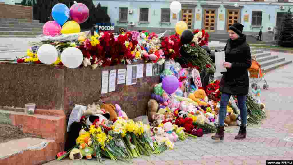 Жители города приносят детские игрушки, цветы, свечи