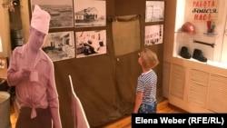Ребенок рассматривает фотографии, посвященные событиям 1959 года, в темиртауском историко-краеведческом музее. 8 августа 2019 года.