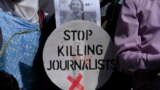 A Pakistani journalist holds a sign and a picture of Associated Press photographer Anja Niedringhaus,, who was killed on April 4, 2014, in Afghanistan, during a demonstration in Islamabad to condemn attacks against journalists.
