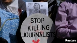 Pakistan -- A Pakistani journalist holds a sign and a picture of Associated Press photographer Anja Niedringhaus, who was killed April 4, 2014 in Afghanistan, during a demonstration to condemn attacks against Journalists in Islamabad, April 7, 2014
