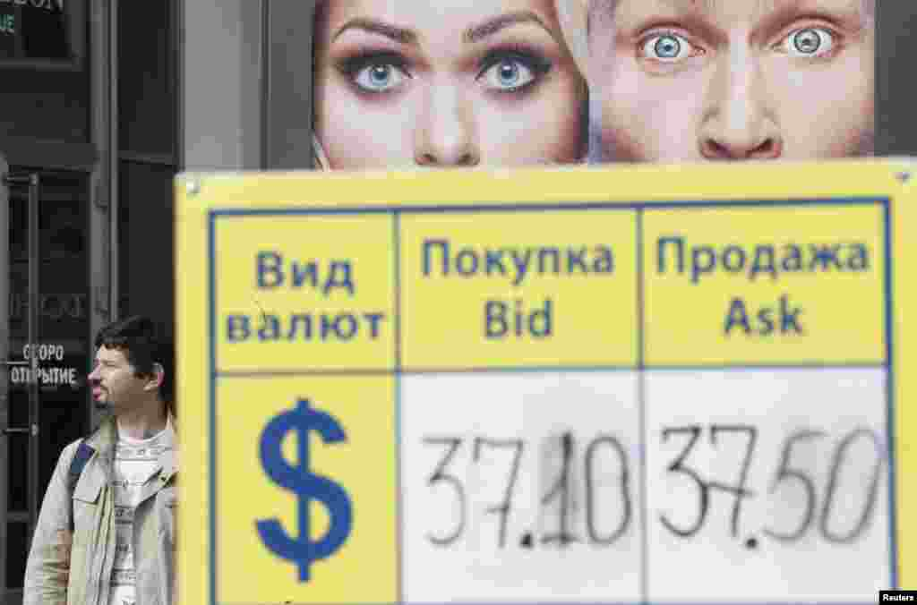A man walks past a board displaying currency exchange rates in central Moscow on September 2. Russian assets fell on September 1, with the ruble hitting a record low against the dollar after Europe and the United States accused Russia of direct military involvement in Ukraine. (Reuters/Maxim Zmeyev)