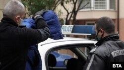 Полицаи водят 22-годишния Кристиан Николов, за да му бъдат повдигнати обвинения на 20 април