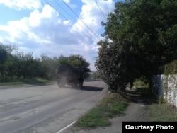 Військова машина у хмарі пилу на роздовбаній дорозі