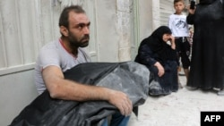 A Syrian man carries the body of his nephew following a reported air strike in Aleppo on September 23.
