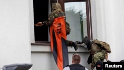 Pro-Russian activists attack the regional administration building in Luhansk on April 29.