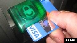 Банкоматқа салынып жатқан банк карточкасы. (Көрнекі сурет)
