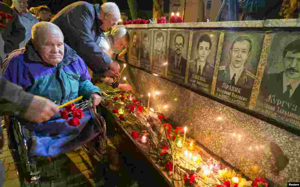 People light candles at a memorial dedicated to firefighters and workers who died after the Chornobyl nuclear disaster during a night service near the Chornobyl plant in the Ukrainian city of Slavutych. Belarus, Ukraine, and Russia marked the 27th anniversary of the Chornobyl disaster on April 26. It was the world's worst civil nuclear accident. (Reuters/Gleb Garanich)