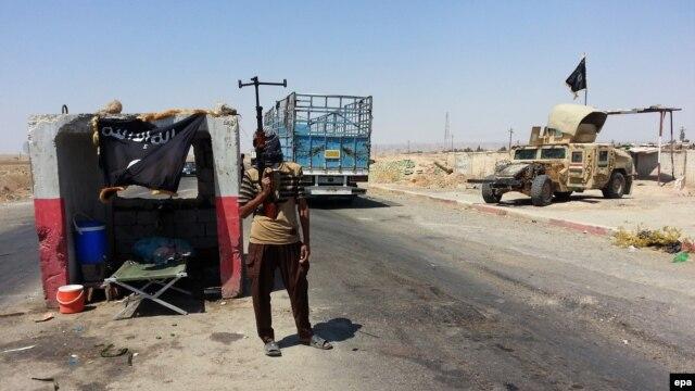 در تصویر یک شبهنظامی در ایست بازرسی ارتش در شهر بیجی، که به تصرف داعش در آمده است