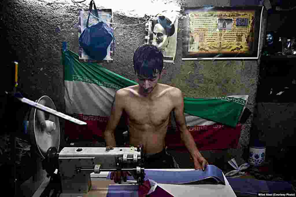 "Alaei took this photo of a young Afghan working at a tailor's shop. ""It was during summer, the weather was warm, and [the Afghan teenager] was not wearing a shirt while working,"" Alaei said. ""Behind him there was a flag of Iran and a picture of Ayatollah Khomeini. I included this in a series of photos of workers and daily life. But I was told it would be removed. When I asked my editor why, he said that because of the [combination] of the picture of Khomeini, the Iranian flag, a shirtless worker, and the poverty shown, it couldn't be published."""