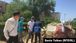 Возложение цветов к камню, к которому прикреплена табличка с надписью: «В память о жертвах политических репрессий». Актау, 31 мая 2017 года.
