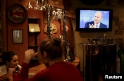 Patrons in a bar in Russia's Stavropol region pay no mind as Putin answers questions from the public on a TV overhead.