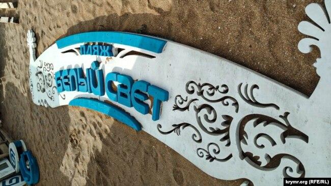 Вывеска пляжа «Белый свет» на песке в поселке Береговое под Феодосией, июль 2020 года