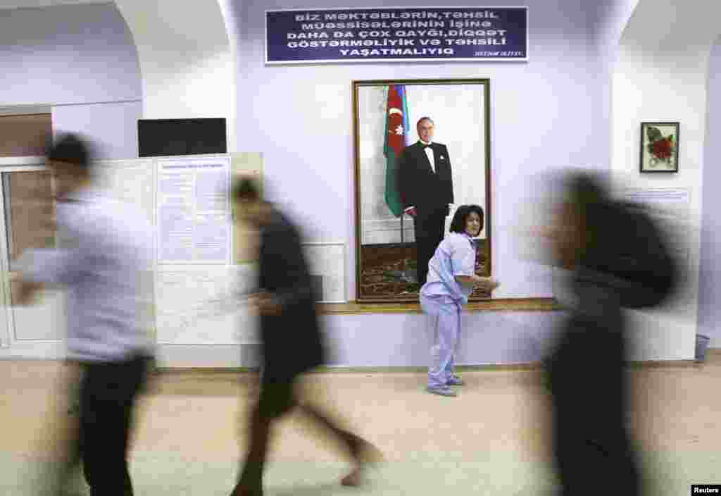 Azerbaijani election officials walk past a portrait of late President Heydar Aliyev at a polling station located inside a school building in Baku. (Reuters/David Mdzinarishvili)