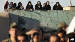 Iranians watch the public execution of a convicted man in the city of Qazvin in May 2011.