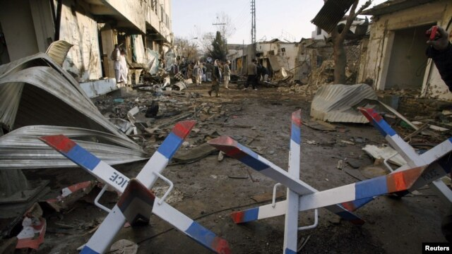 People inspect the site of one of the bomb blasts in Quetta that killed more than 80 people on January 10.