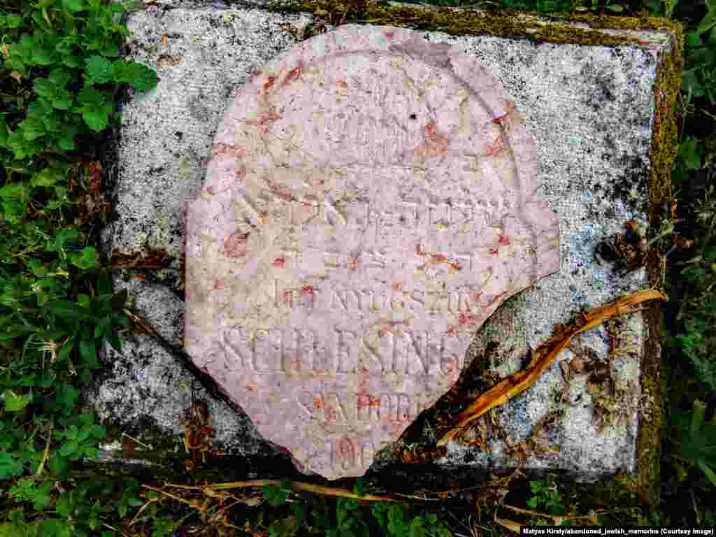 """A broken headstone for a 4-month-old infant in a cemetery near Budapest. Kiraly discovered the vandalized fragment and placed it on a small plinth. An Instagram follower commented, """"His name was Shlomo (Solomon). Thank you for repairing this memory."""""""