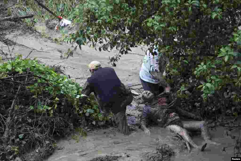 People try to help a man during heavy flooding in the Bulgarian city of Varna on June 19, which killed at least 12 people. (Reuters)