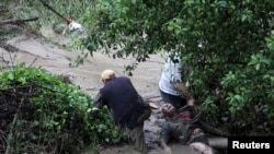 People try to help a man in distress during heavy flooding in the city of Varna on June 19.