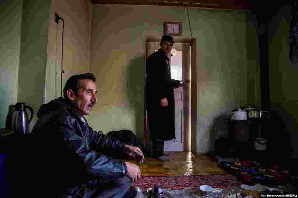 Nazar Boberov, the great-uncle of Umarali, and a relative have tea before visiting the child's grave in the village of Boboi Vali.