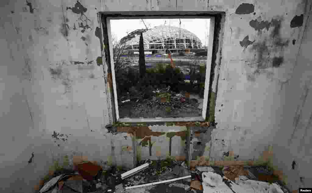 A look through the window of a house that has to be torn down as it is within the perimeters of the Olympic Park shows the stadium for the Sochi 2014 Winter Olympics at Olympic Park in Adler, near Sochi, Russia. (Reuters/Kai Pfaffenbach)