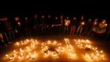 سوريون يتجمعون حول صور ضحايا الحرب تحت الشموع في ليلة رأس السنة الجديدة - حلب 31 كانون الأول 2014