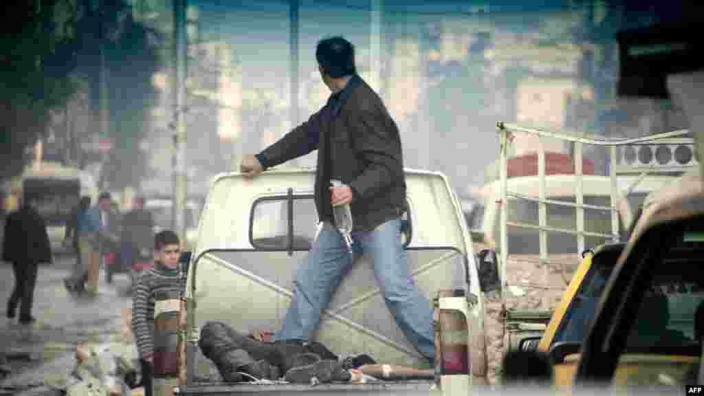 A wounded rebel fighter lies in the back of a pickup truck making its way to a hospital through traffic in the northern Syrian city Aleppo. (AFP/Odd Anderson)