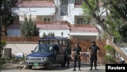 Policemen stand guard outside the house where Osama bin Laden's family is believed to have lived in Islamabad.