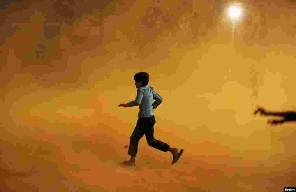 A boy runs for cover during a dust storm in New Delhi. (Reuters/Adnan Abidi)