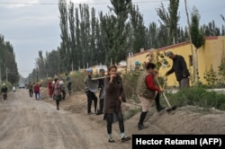 Люди работают на улице уйгурского села. Синьцзян, 13 сентября 2019 года.