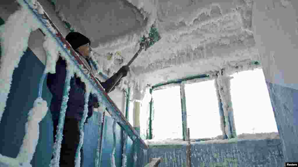 A man removes ice in a stairway caused by a broken sewage line in an apartment block in Karaganda, Kazakhstan. Temperatures dropped to minus 59 Celsius in the eastern region of the country. (Reuters/Valery Kaliyev)