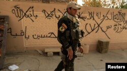 """An Iraqi soldier walks past graffiti, which reads: """"Islamic State will remain,"""" in Bartilla, east of Mosul, on October 27."""