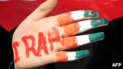 Iran -- A female student holds up her hand painted in the colours of her national flag during a rally on Tehran's Azadi Square to mark the 35th anniversary of the Islamic revolution, February 11, 2014