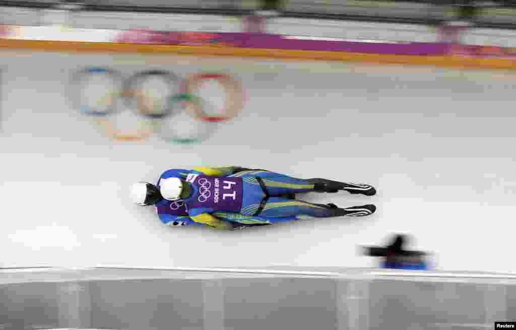 Ukraine's Oleksandr Obolonchyk and Roman Zakharkiv speed down the track during a men's doubles luge training session in the Sanki Sliding Center.