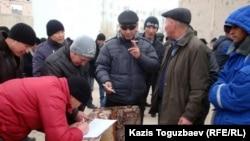 """Бастующие нефтяники компании """"Каражанбасмунай"""" подписываются под заявлением о том, что они не согласны с планами правительства по их трудоустройству в других регионах Казахстана. Актау, 23 декабря 2011 года."""