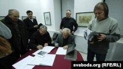 Складальнікі Віктар Маркавец і Уладзімер Крукоўскі падпісваюць кнігі.