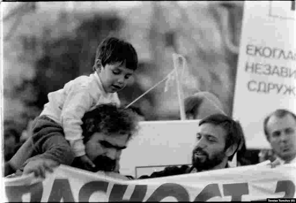 """Петър Стайков (вляво) с тригодишния си син Свилен и Красен Станчев на шествието на """"Екогласност"""" на 3 ноември 1989 г.""""На тази дата започна превръщането на поданиците на тоталитарната държава в граждани"""", каза неотдавна Петър Стайков пред БГНЕС. """"Без този период на трансформация от едното качество в другото, нямаше да имаме нищо от това, което имаме сега, колкото и някои неща да не ни харесват"""". Психологът Петър Стайков е депутат във Великото Народно събрание (1990-1991) и съавтор на конституцията."""